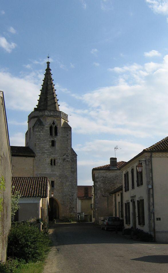 Une élégante tour-clocher est bien fichée en terre, abritant le porche d'entrée. Elle est surmontée d'une flèche en pierre à base hexagonale qui s'élance vers le ciel.
