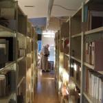 Photo prise entre deux rayons de livres. Un frère est en train de chercher une référence dans les fichiers de la bibliothèque.