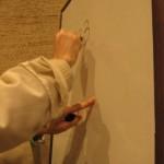 Une main de moine écrit sur un tableau blanc.