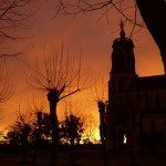 Aube d'un matin d'hiver. La Grande église, vue de la place, apparait en ombre sur fond d'un ciel orangé.