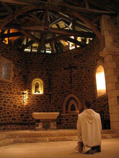 Un moine prie dans la chapelle. On aperçoit vers le haut la charpente traditionnelle des vieilles églises landaises.