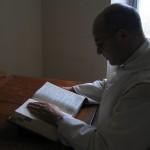 Un frère lit la Bible à son bureau, à la lumière du soleil.