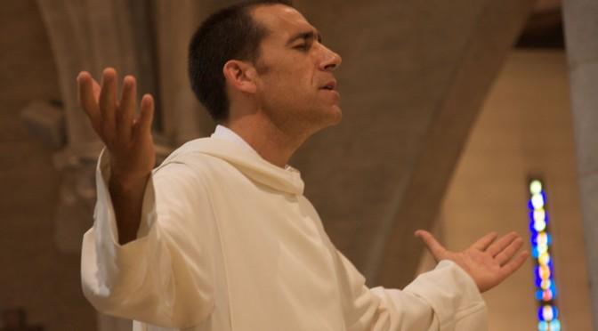 Un moine chante les bras levés lors de sa profession