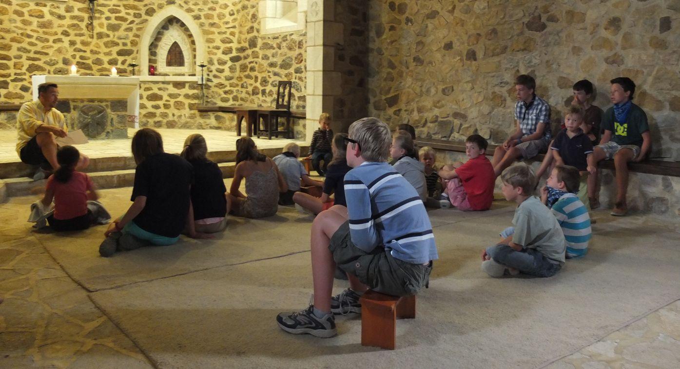 Des enfants écoutent un adulte dans la vieille église