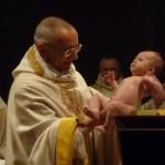 Le père abbé tient un bébé dans ses mains, à la sortie de la cuve baptismale.
