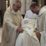Le père abbé remet une coule