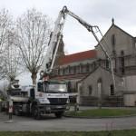 camion envoyant du béton dans l'église au bout d'un long tuyau
