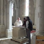 un moine et deux artisans travaillent