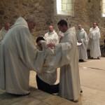 Le père abbé et le maitre des novices mettent habillent le postulant