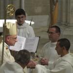 l'ordinant a les mains jointes dans les mains de l'évêque