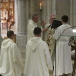 l'évêque a les mains étendues sur ceux qui sont ordonnés, à genoux devant lui