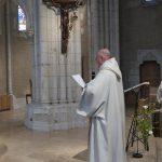 frère colomban de profil lit sa charte sous la croix