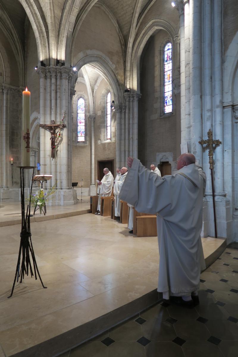 Fr Comlomban les bras levés à l'entrée du choeur