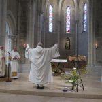 Fr Comlomban les bras levés devant l'autel